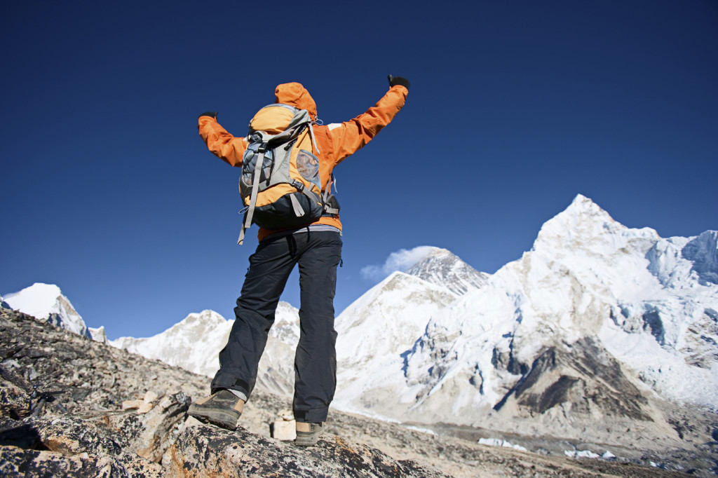 Female trekker looks over Himalayas
